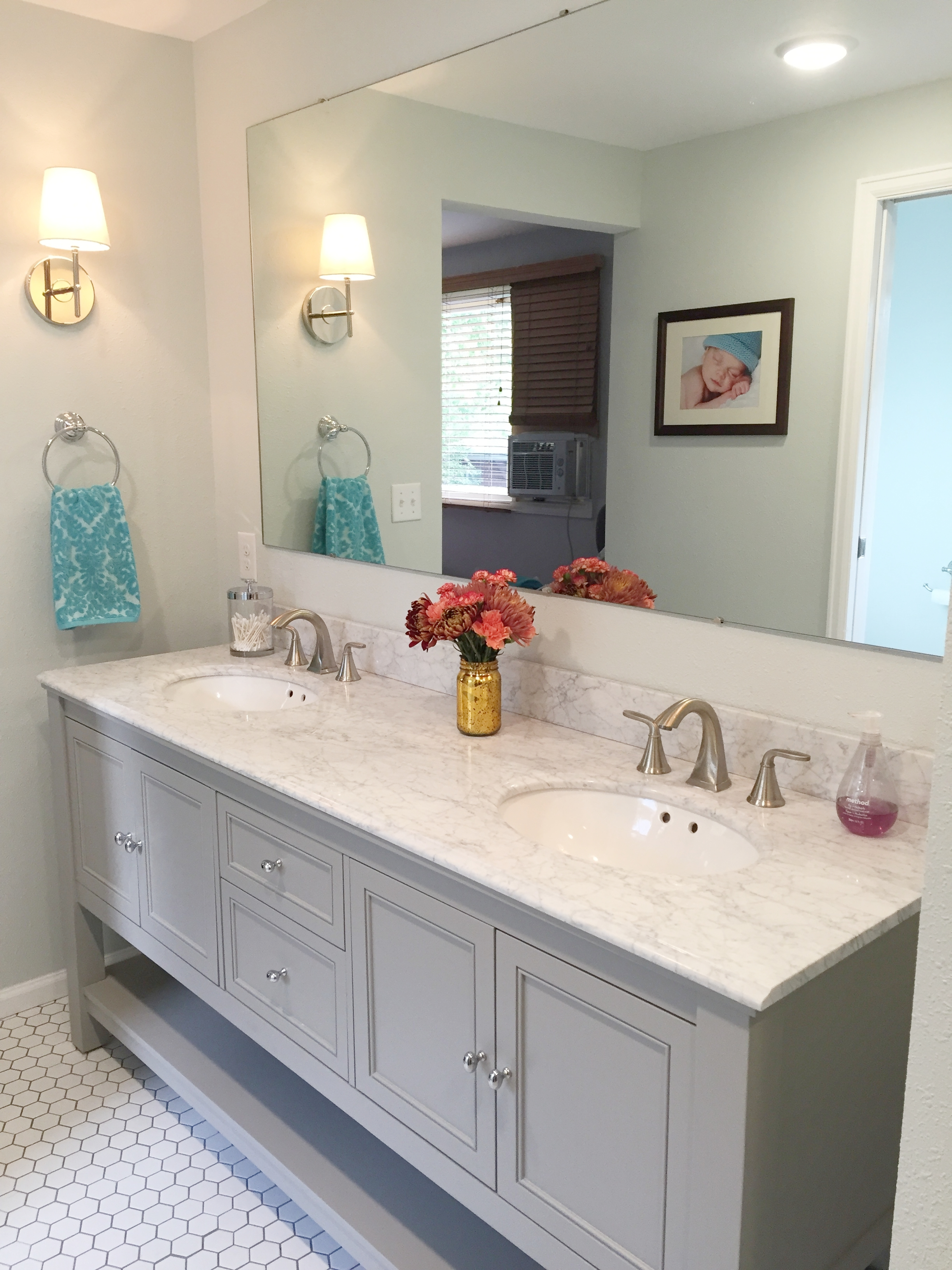 The double sink vanity has a marble countertop and the sconces are West Elm.