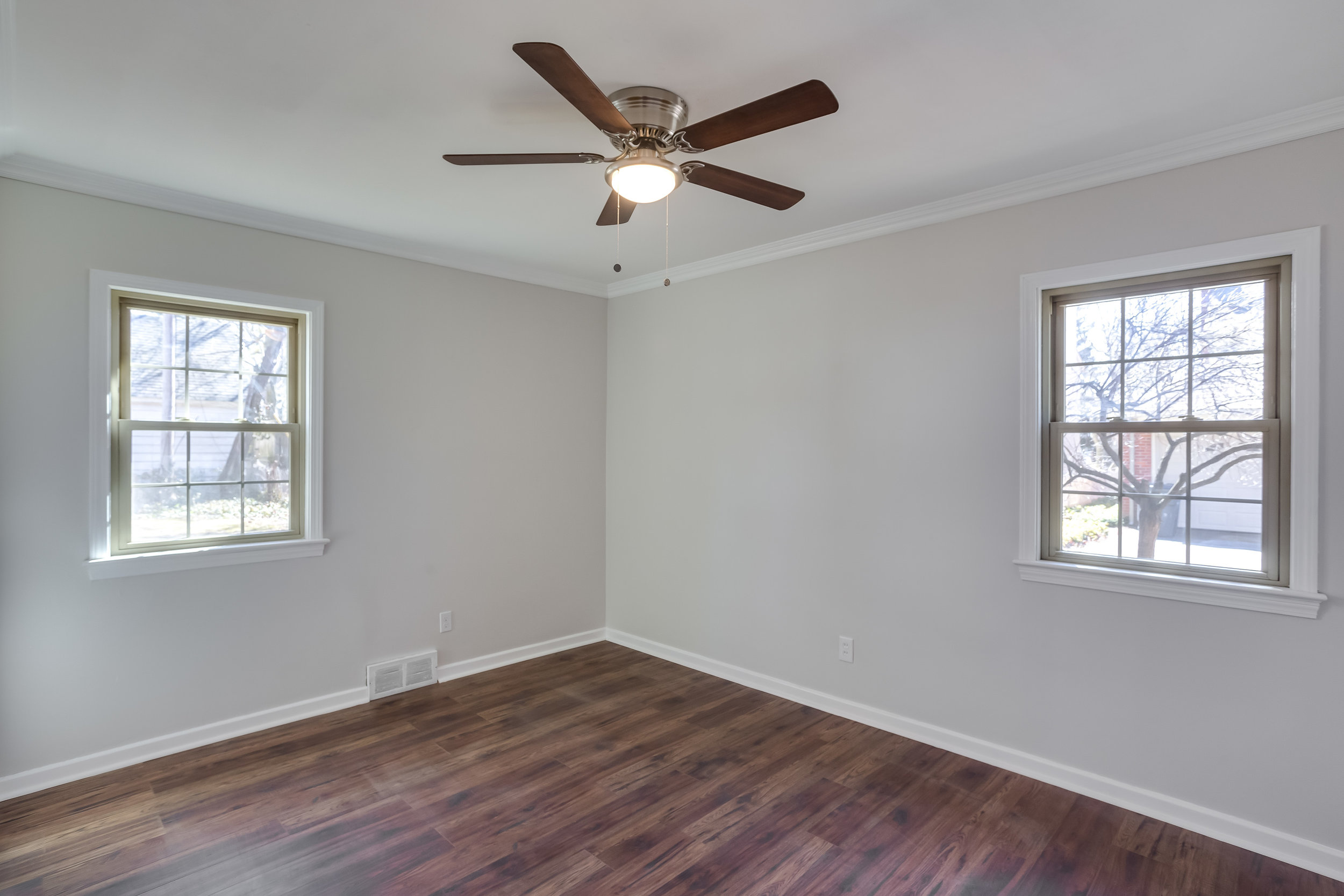 After, the bedroom is clean with fresh paint and new vinyl plank wood floors and a new ceiling fan.