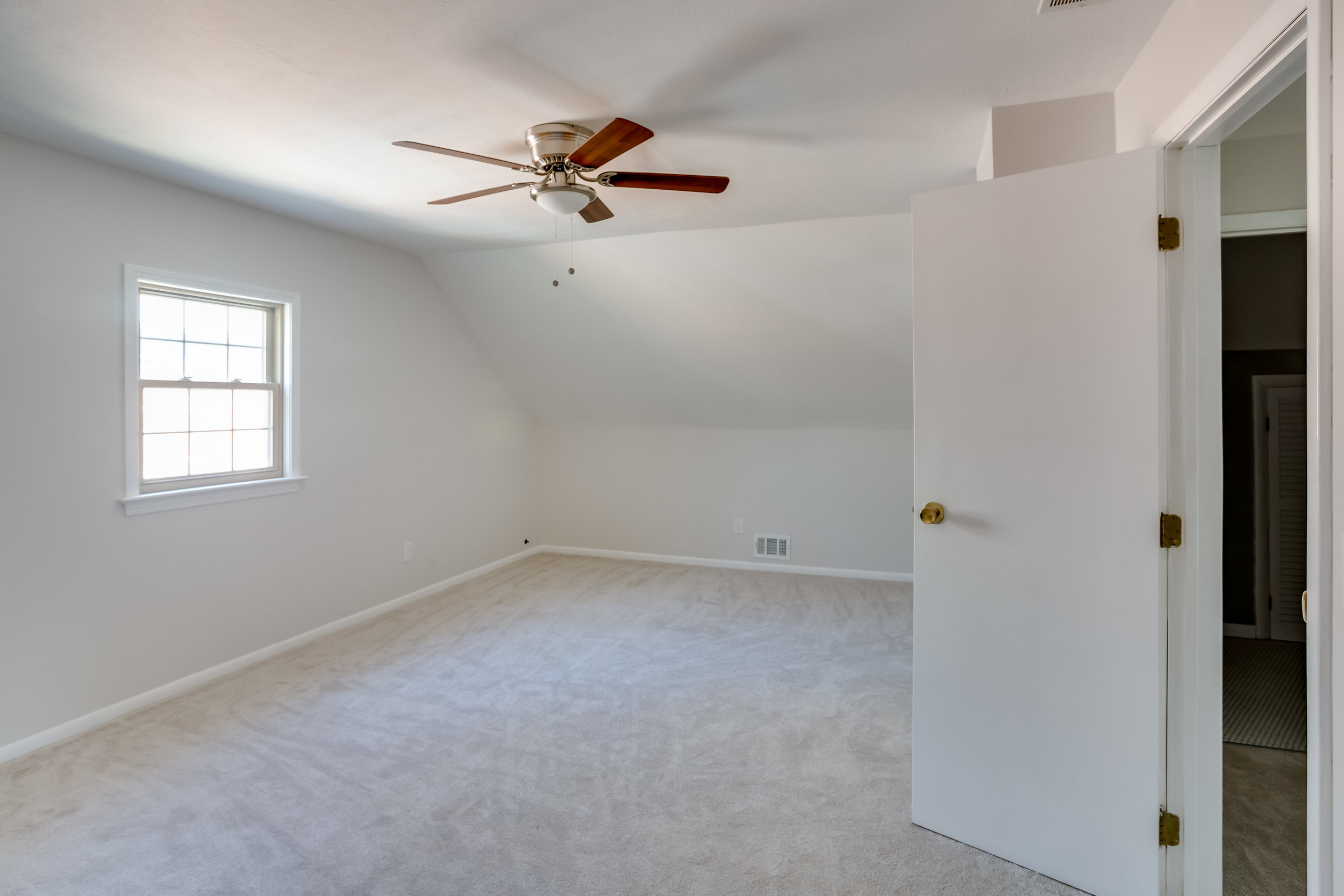 After, the walls are smooth and painted a neutral color, the carpet is new and a modern ceiling fan was installed.