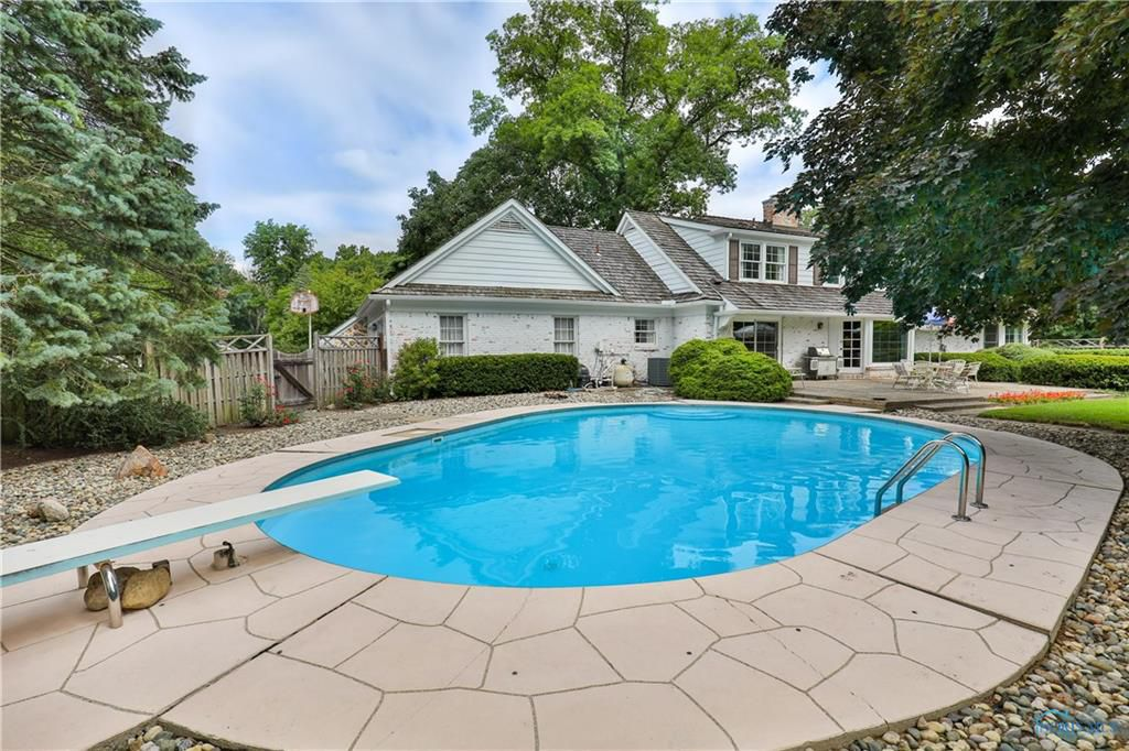 The backyard includes a built in pool with a diving board.