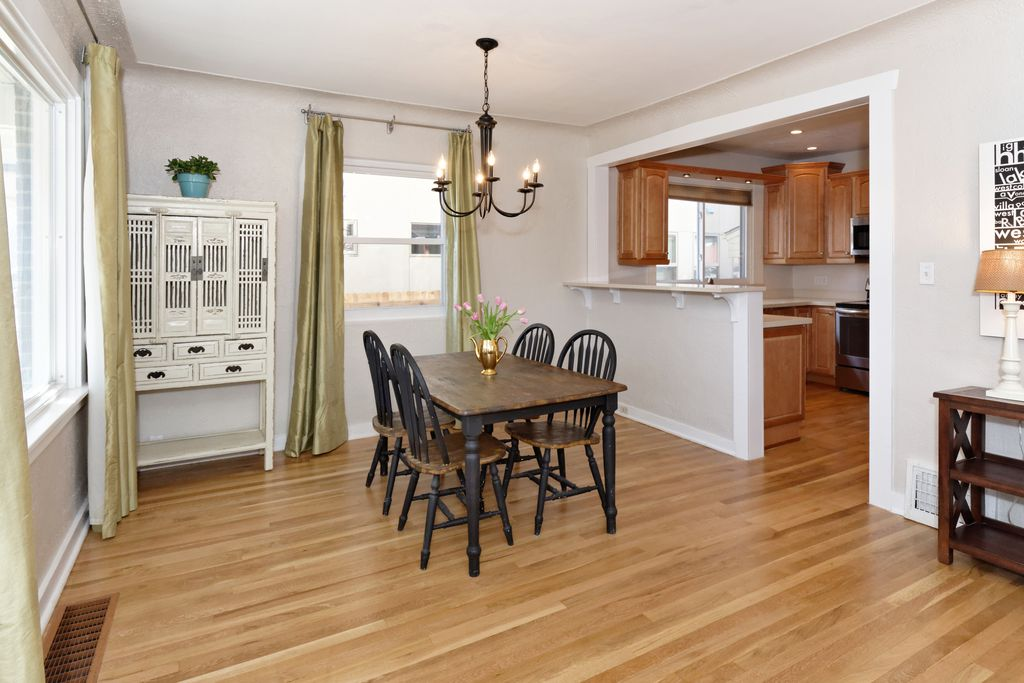 The dining room is now open to the kitchen with a breakfast bar. The new light fixture modernizes the space.