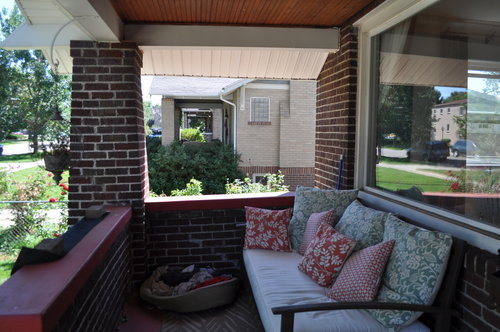 The front porch had red concrete, a dark bead board ceiling and vinyl siding on the peak of the porch.