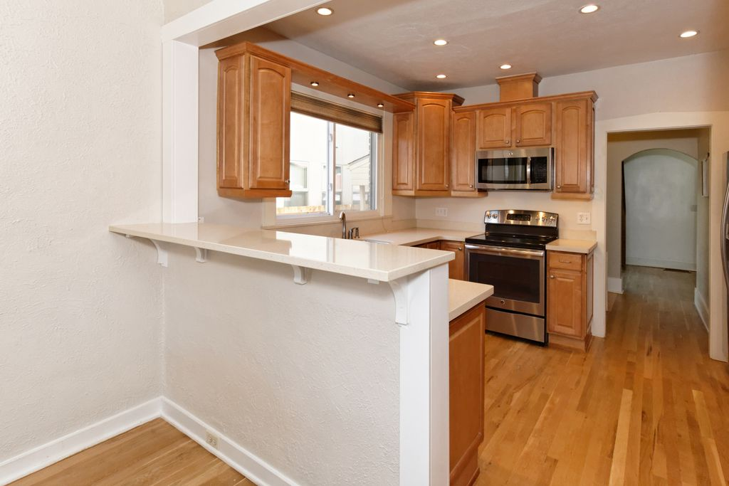 The kitchen is now visible from the dining room with the new breakfast bar installed. Carrying the same paint color from the dining room into the kitchen gave the illusion of a larger space. The stainless steel appliances complete this renovation.