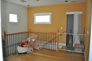 The top of the stairs had a bright orange accent wall that needed to be painted over with a neutral color.