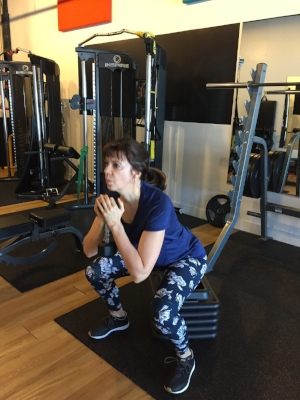 Lucie practices her squat form with extra focus on driving her knees out and keeping her chest up.