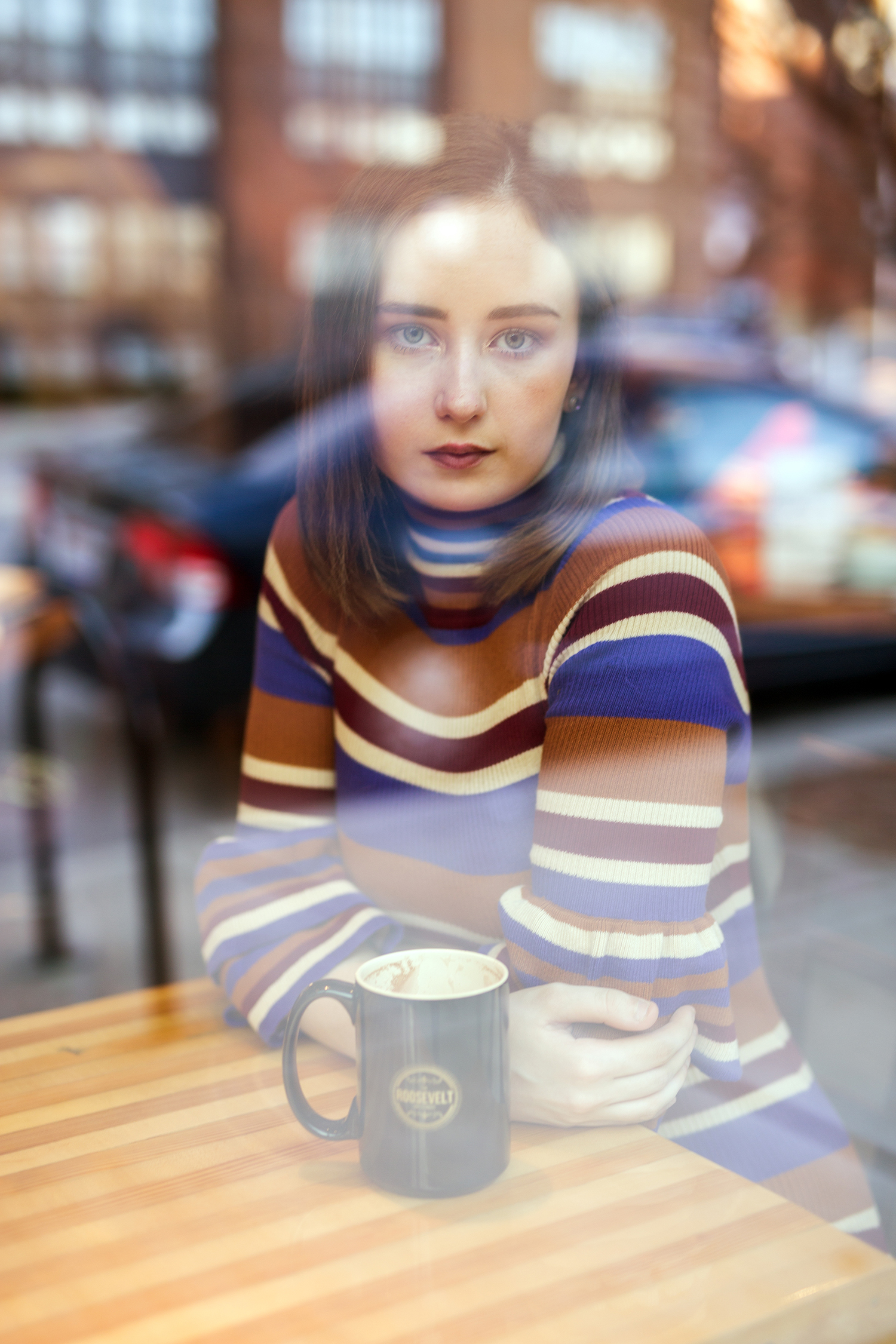photograph through the window of a girl sitting at a table with hot chocloate
