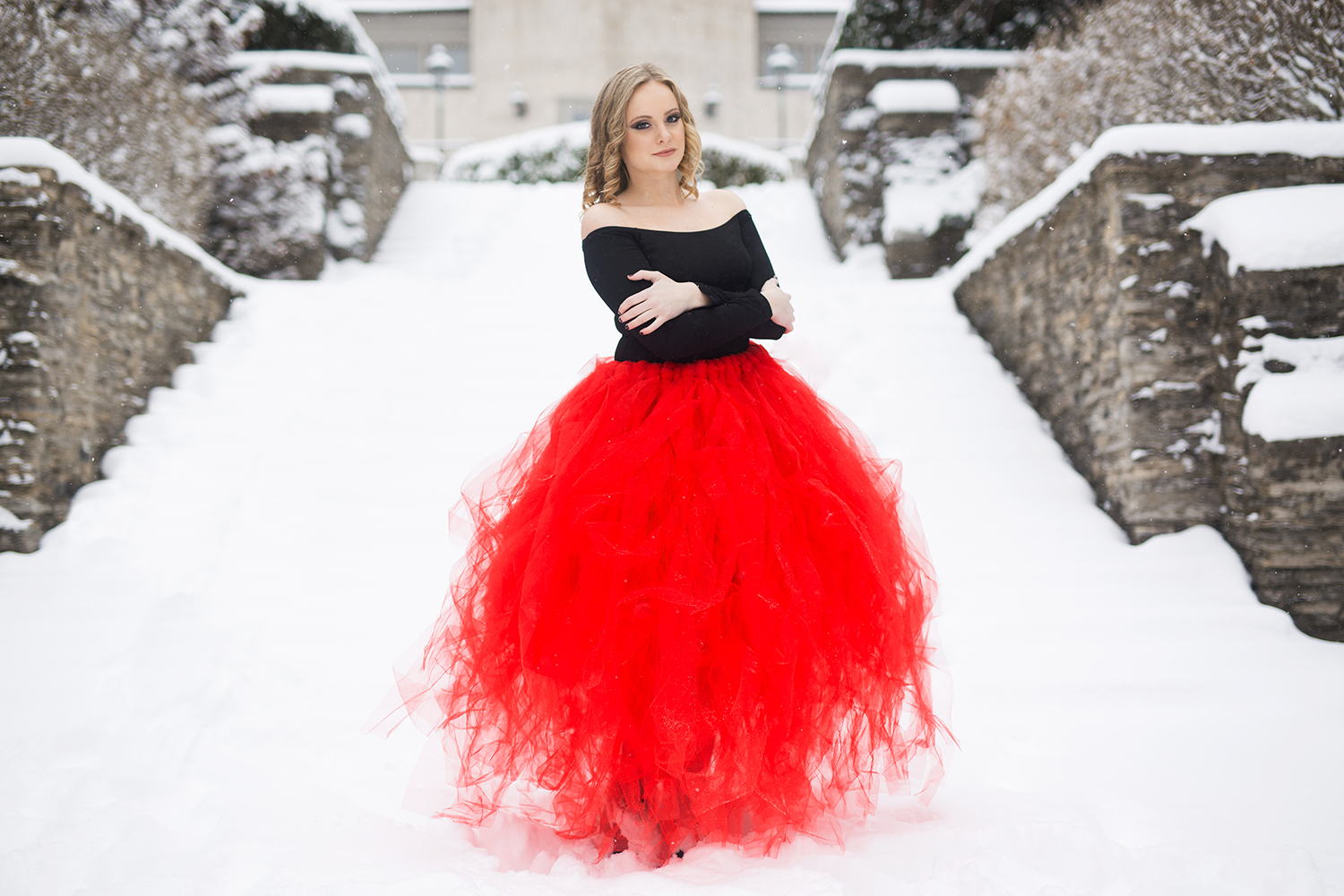 Anna posing in a red tulle skirt in the snow.