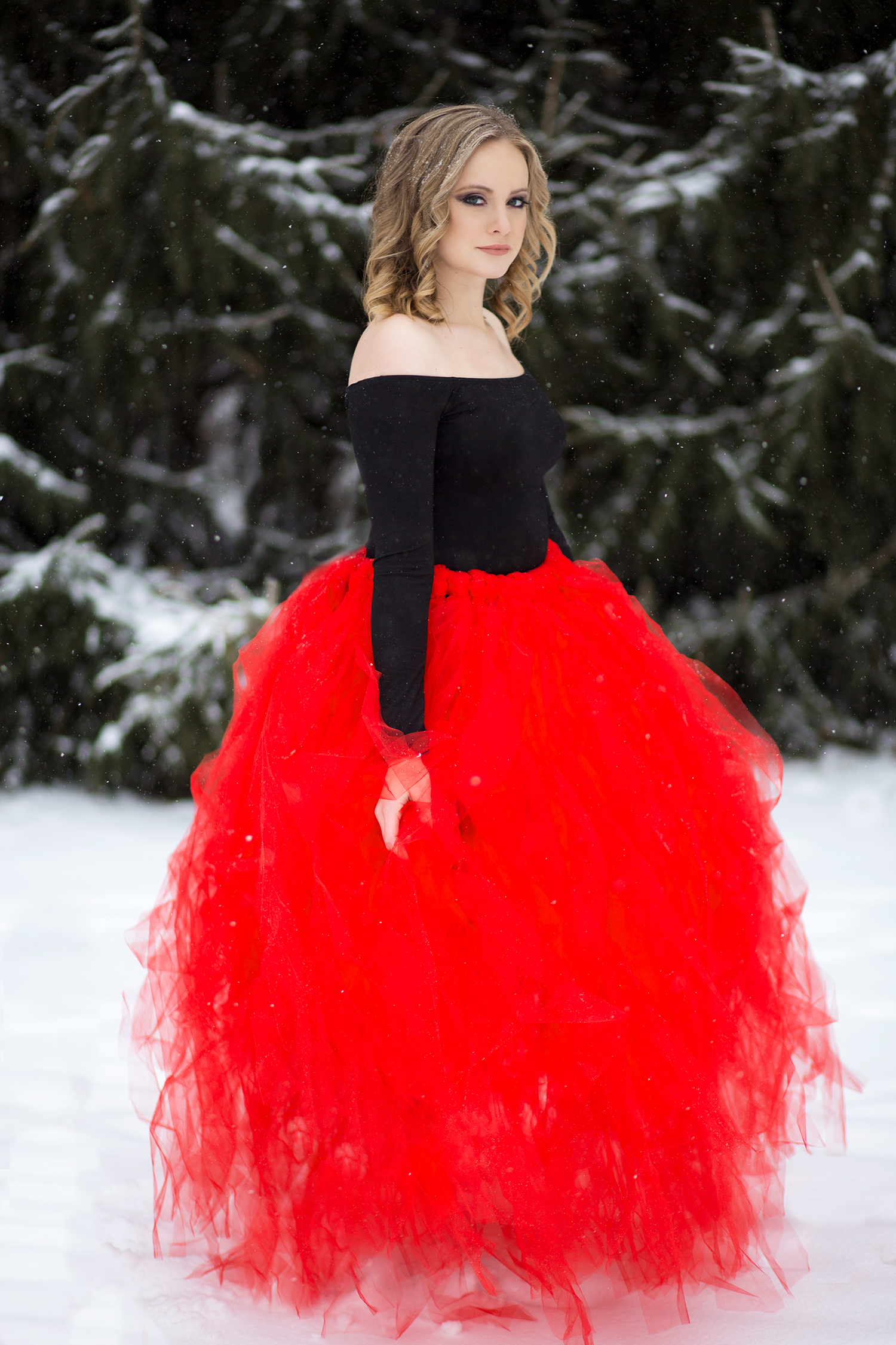 A girl in a red tulle skirt and black off the shoulder top posing in the snow.