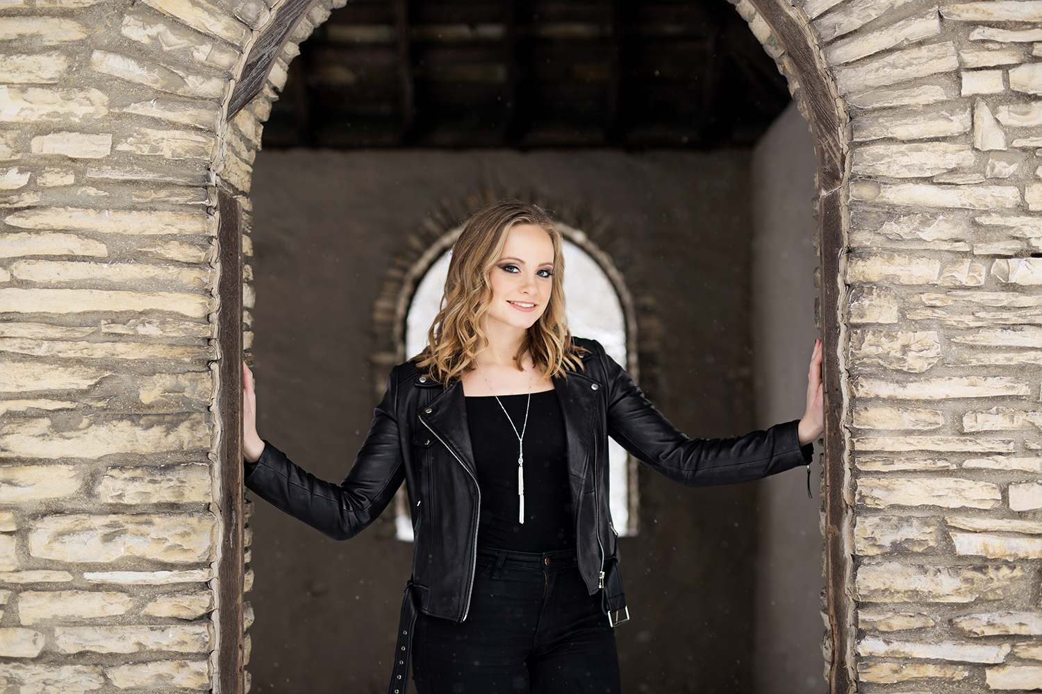a senior in all black posing in between a stone an arch way.