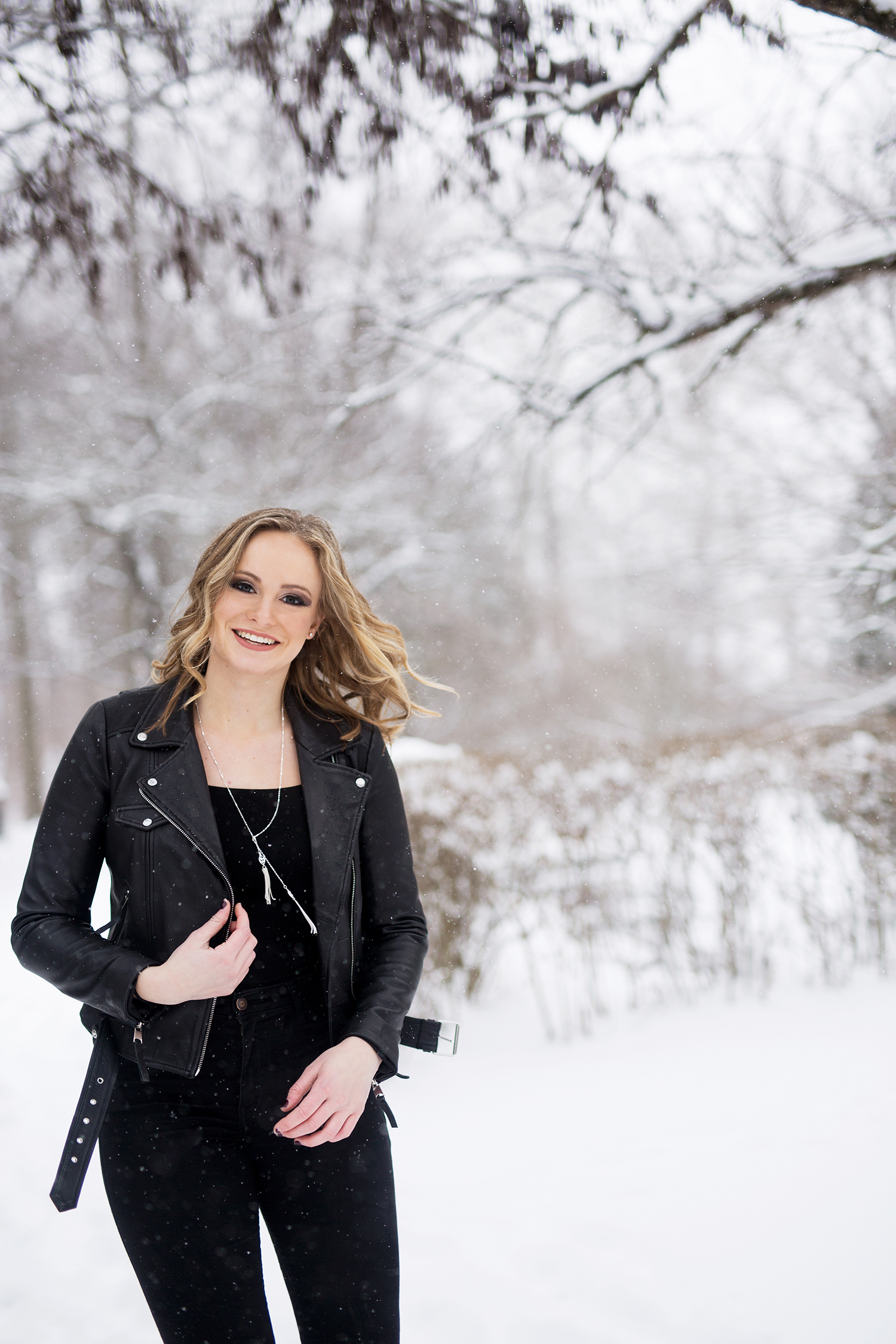 a girl in all black smiling in the snow.