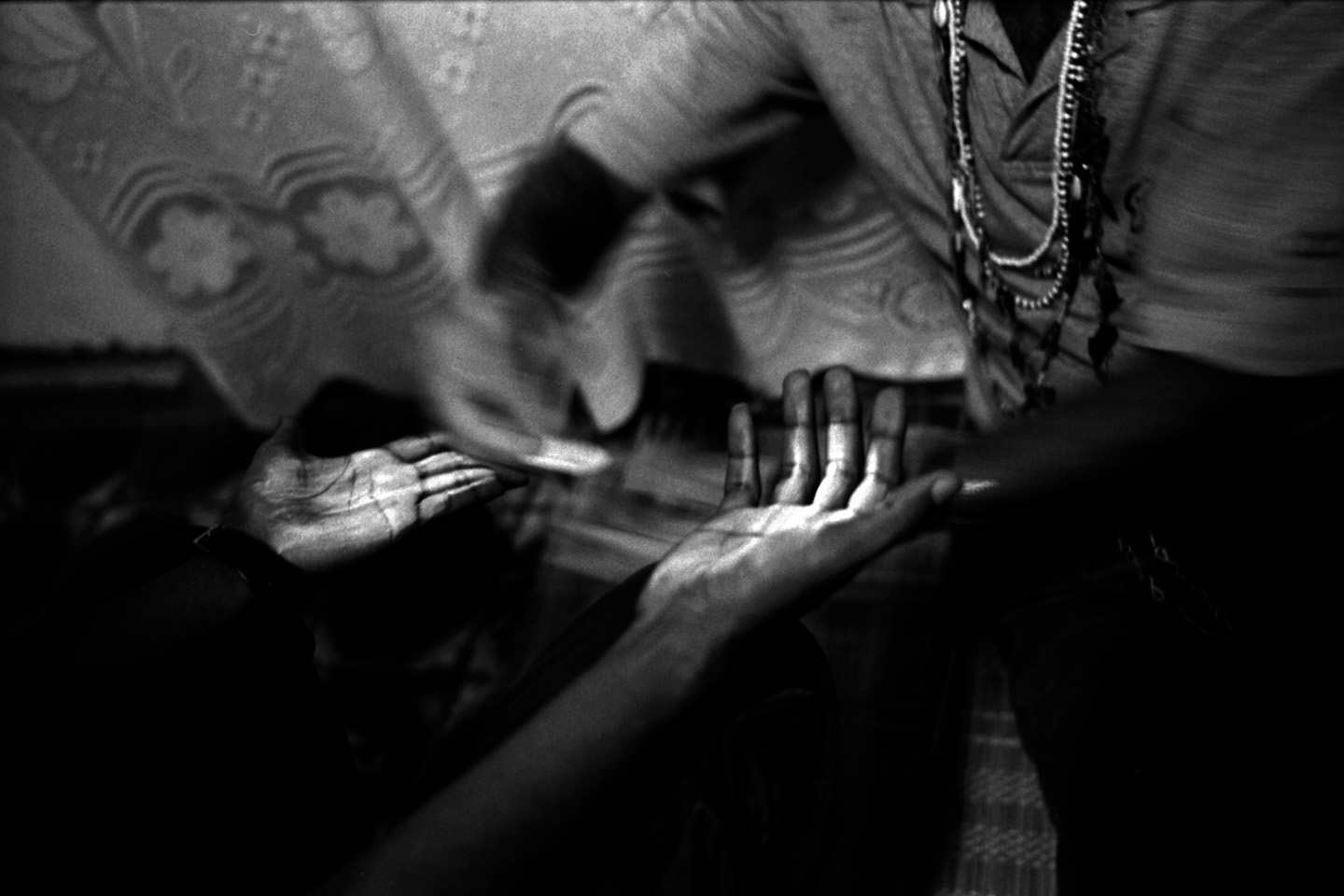 A babalawo begins the Santeria ceremony by rubbing chalk on a man's hands. Havana, Cuba.