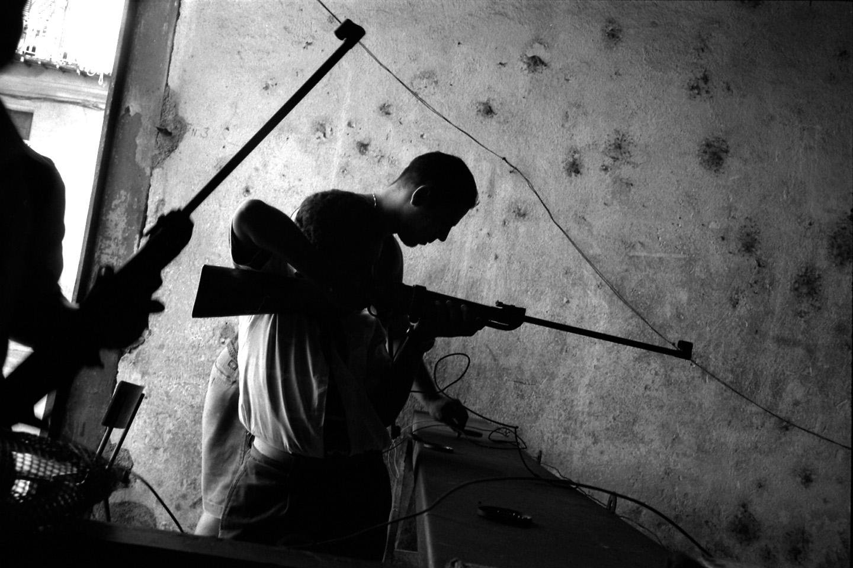 A group of schoolboys practice target shooting at a recreational gun range. Havana, Cuba.