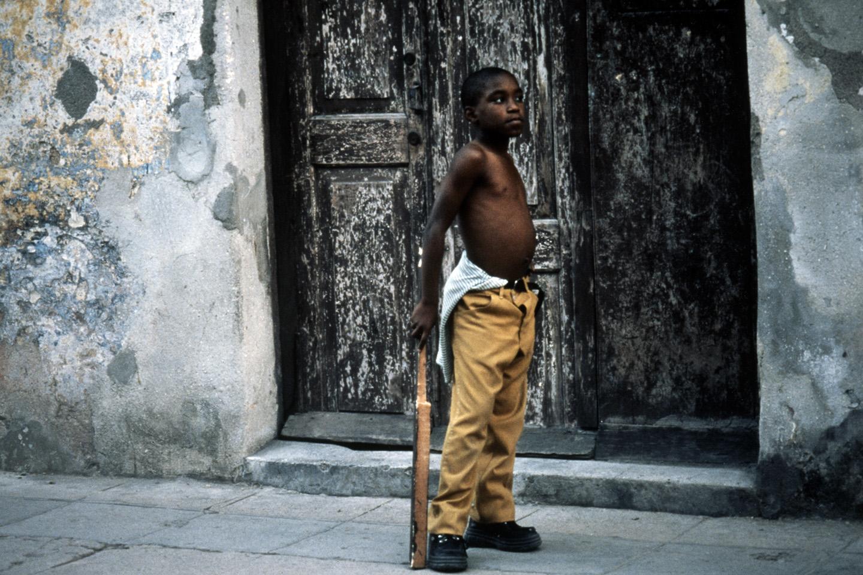 Boy with a makeshift baseball bat, Havana, Cuba.