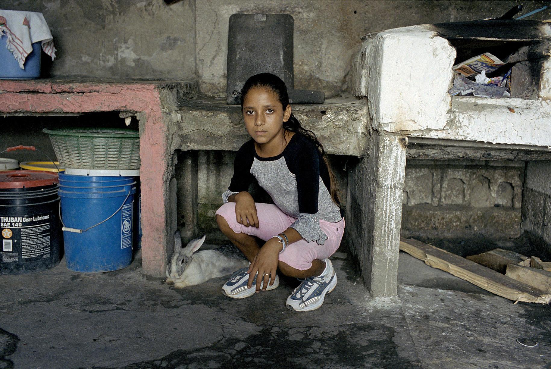 A young girl with her pet rabbit, El Salvador.