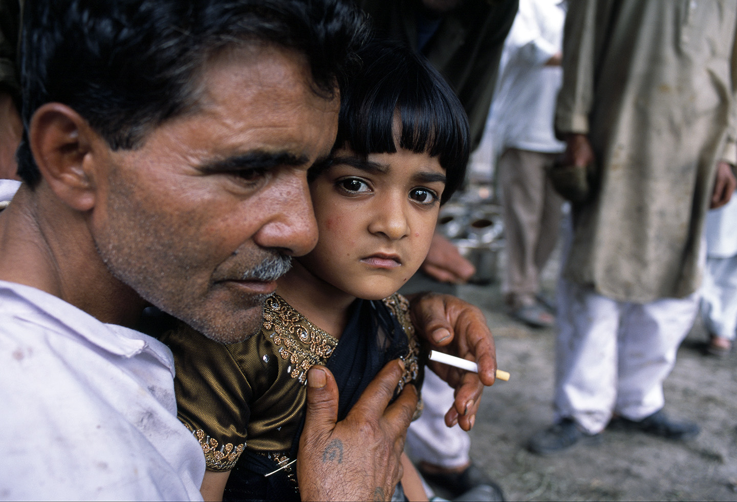 A father rests with his daughter, Kashmir.