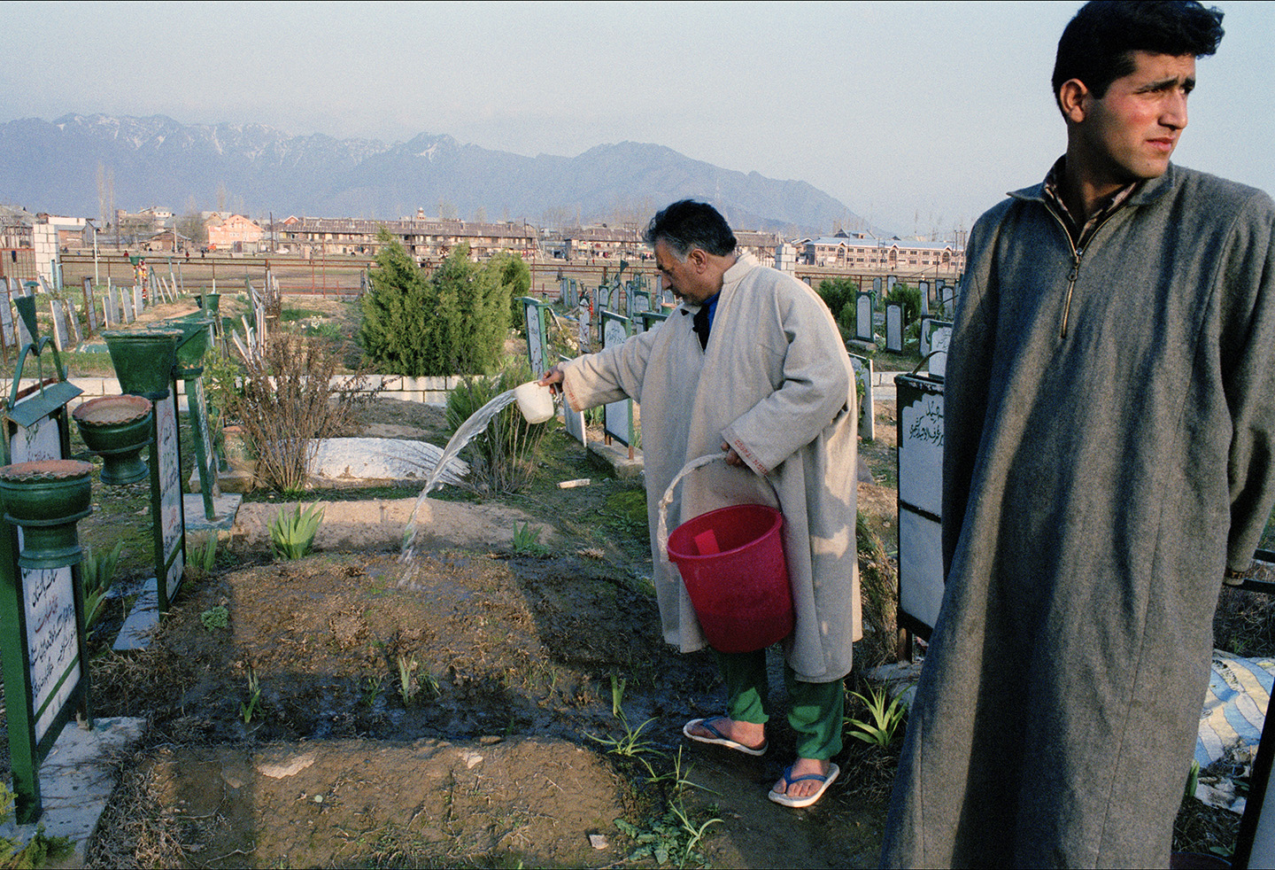 Mohd Shafi Bazaz waters the flowers on his son's grave every four days, Kashmir.