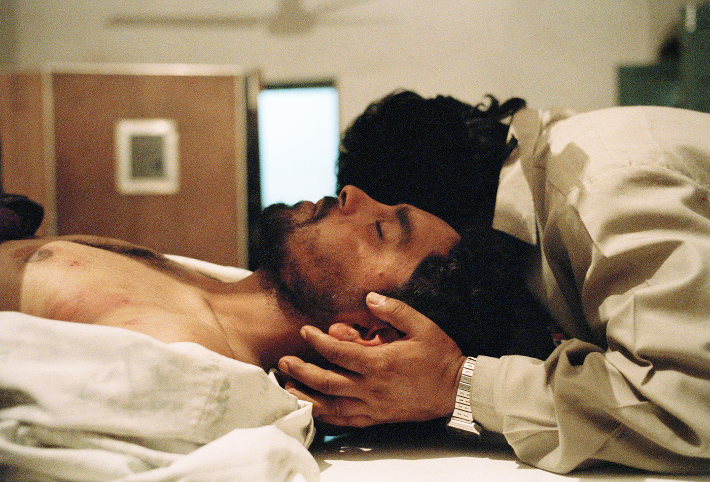 A torture victim is embraced by his brother at a hospital head trauma unit, Kashmir.