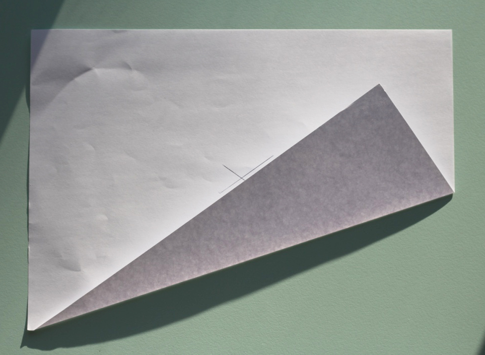 Fold den ene langside fra hjørnet og ind over mod krydset, så papirkanten flugter med den ene linje i krydset.