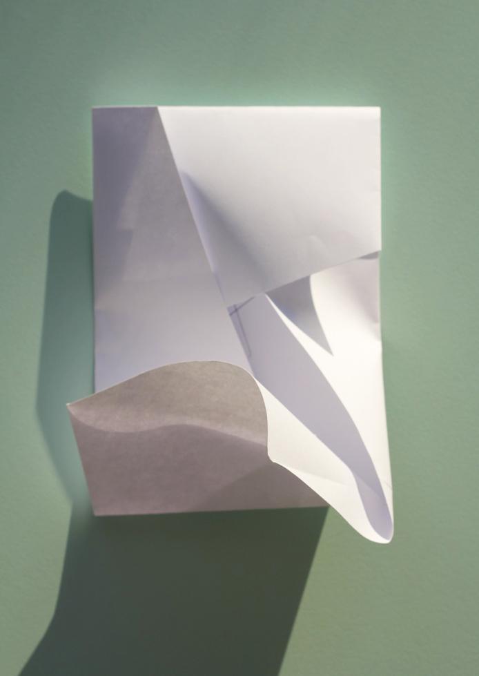 Fold den anden kortside ind mod midten og gør plads til at hjørnet kan skubbes ind og lukke konvolutten. (Samme princip som med en papkasse).