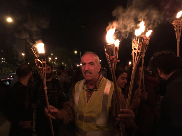 Protestors carry torches at a protest in Ramlet al-Baida on November 15, 2016. (Kareem Chehayeb)