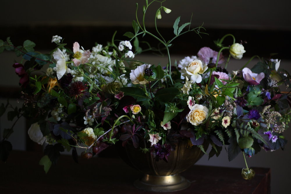 wedding centerpiece featuring gooseberries, potentilla fructicosa, ferns, Crocus rose, Phyllis Bide rose, 'Rubenza' cosmos, Physocarpus 'Diablo', Japanese anemone, sweet peas on the vine, iceland and mother of pearl poppies, phlox 'Cherry Caramel' and phlox 'creme brulee', clematis seed heads and lots of textural elements