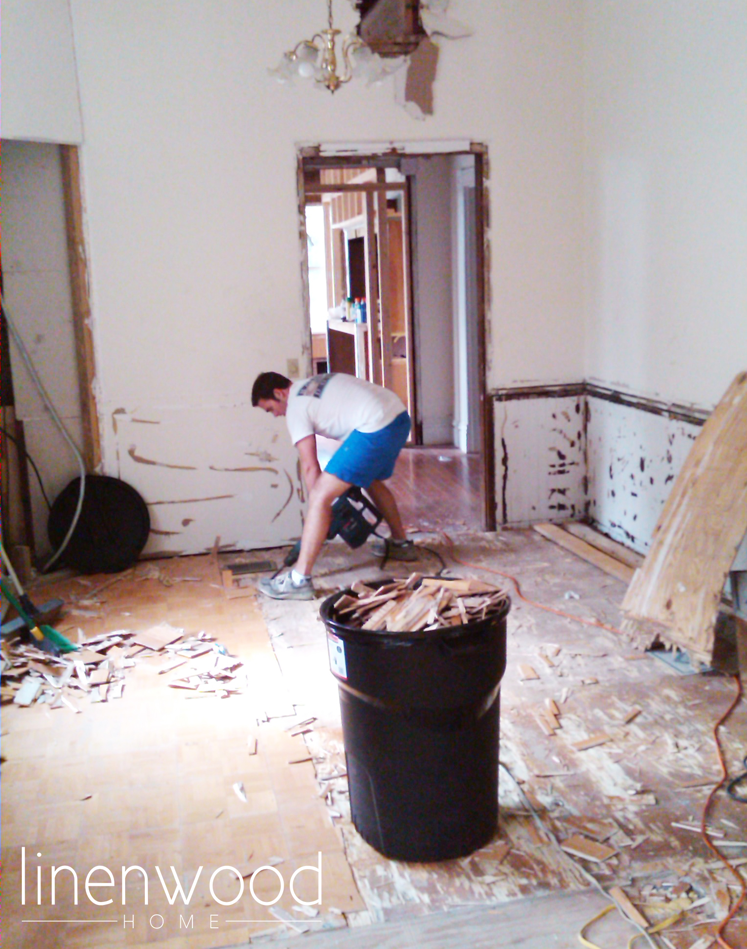 Robby working through all the random layers of flooring in the dining room. We did gain about 2 inches when it was all removed though!