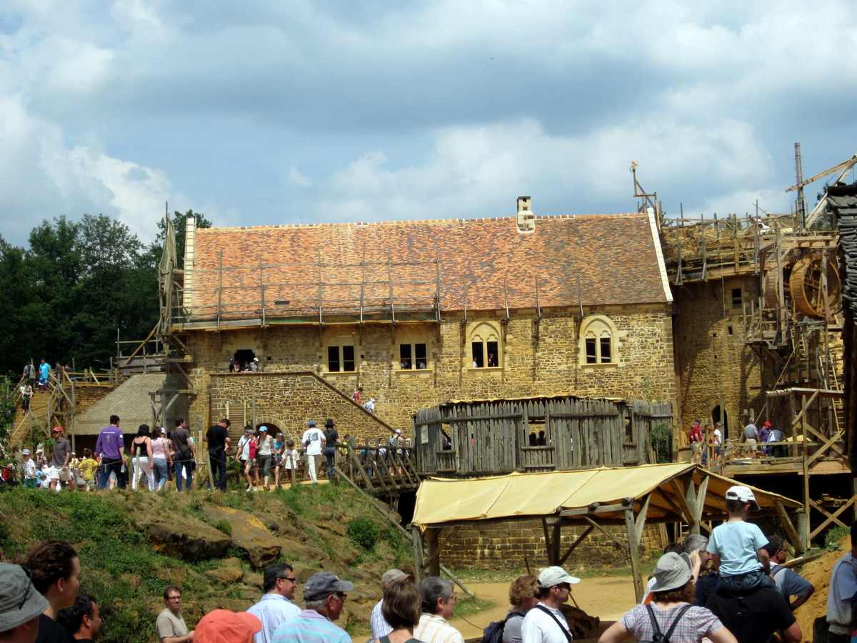The main entrance to Guédelon castle under construction on June 3, 2011, Burgundy, France. The Great Tower is on the right and the Chapel Tower can just be seen on the left, slightly behind the residence. The bridge in the foreground spans the ditch, which will become a moat. One gate tower is to the right.