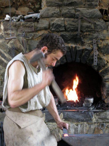 The blacksmith, Martin Claudel, pounding an iron tool into shape.