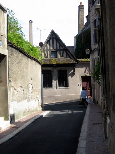 A man carries his shopping home along a narrow street in Auxerre.