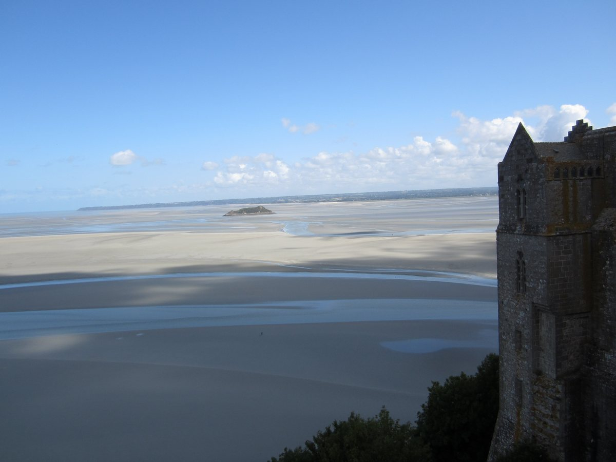 Looking out from the top of Mont Saint-Michel. The sand flats lead out to the ocean in the background. In the foreground is one of the towers added to the abbey in the 19th century .