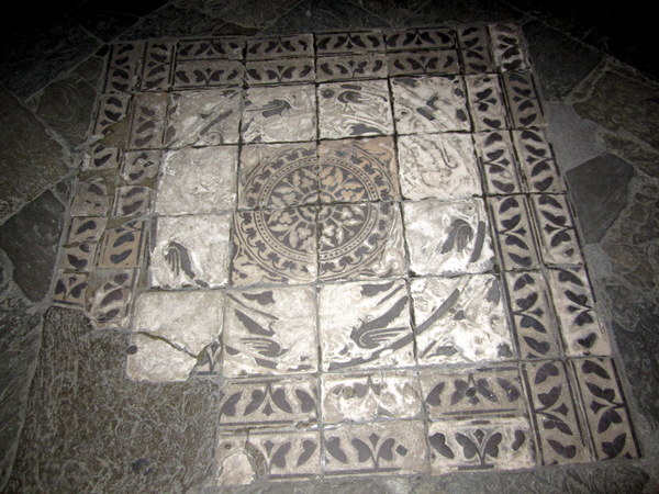 An ancient mosaic on the floor of an entranceway, worn from the treading of thousands upon thousands of feet.