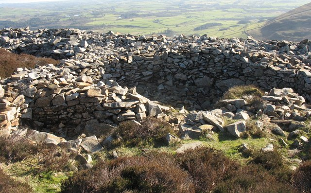 To help with imagining what a hill fort looks like: The remains of a hill fort in Gwynedd, Great Britain.  Round hut bases at the SE end of the Tre'r Ceiri hill fort   cc-by-sa/2.0  - ©  Eric Jones  -  geograph.org.uk/p/690634