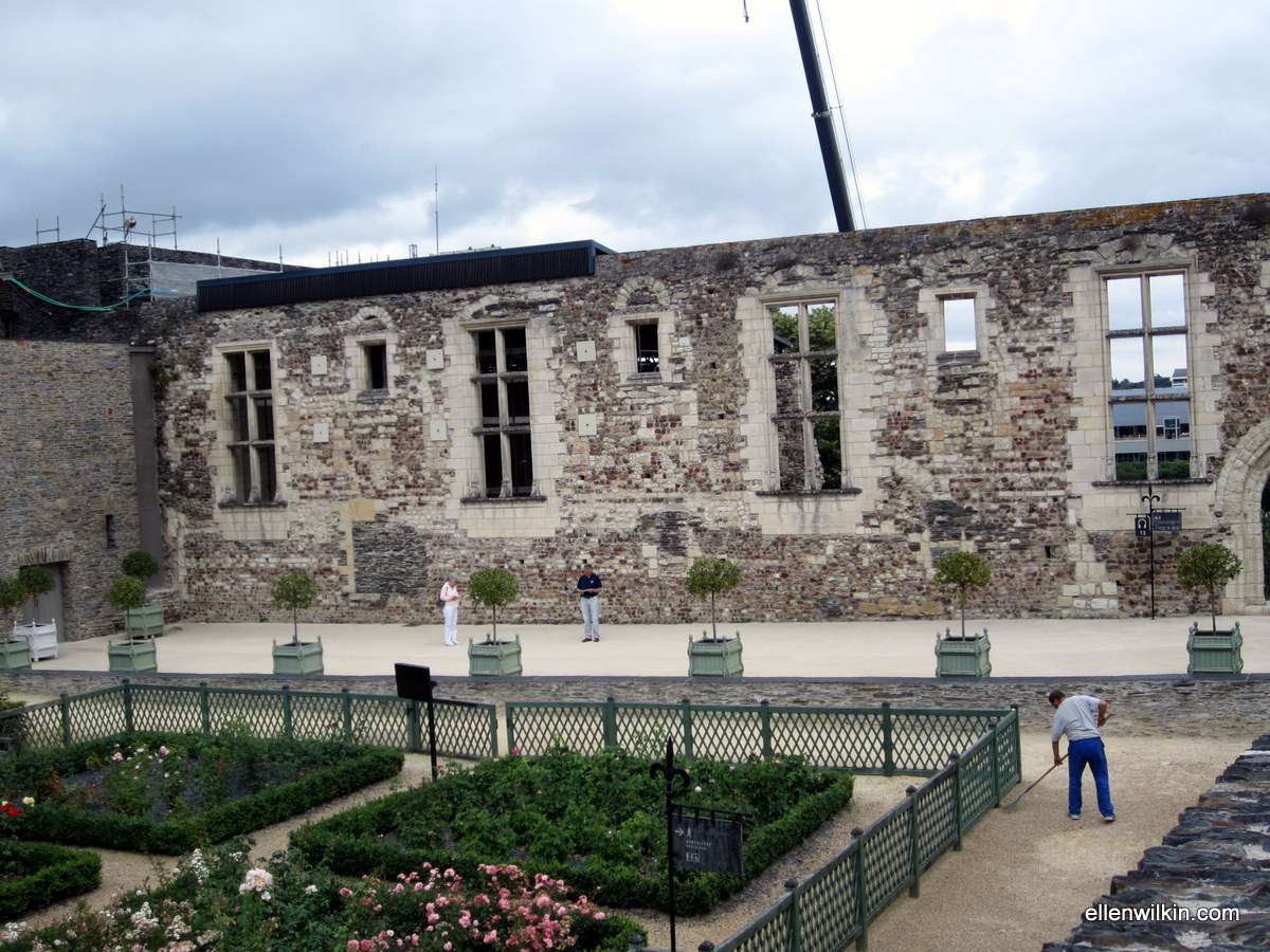 The manicured gardens in front of the original 12th-century wall of the Chateau d'Angers. These gardens are enclosed on the opposite corner by the new Apocalypse Tapestry wing. You can just see one wall of that wing coming in to meet the old wall at the top left of the photo.