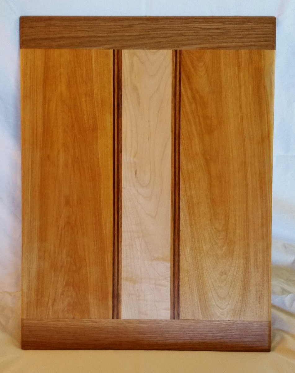 Beautiful red birch surrounds wavy maple with black walnut and cherry stripes all bound with white oak breadboard ends