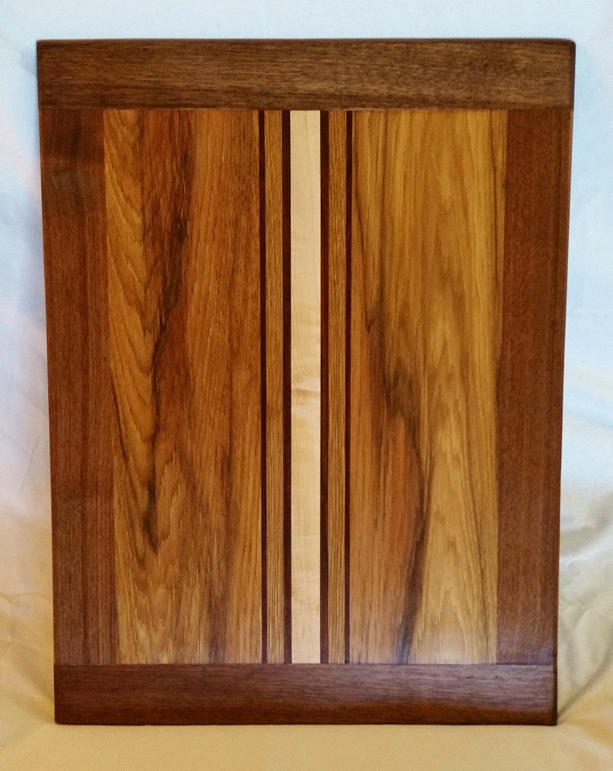 This warmly rich serving board has a select heartwood from hickory with black walnut, wavy maple, and white oak