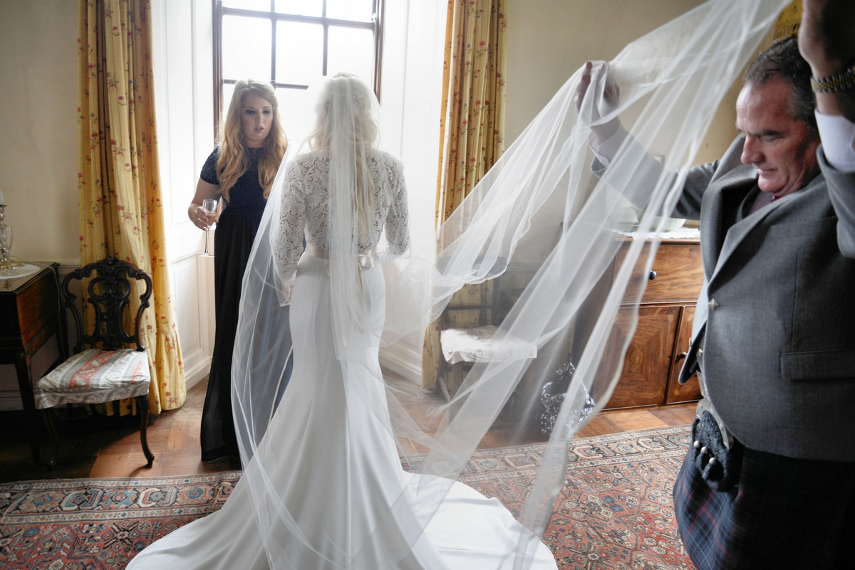 Father of the bride helping with the veil