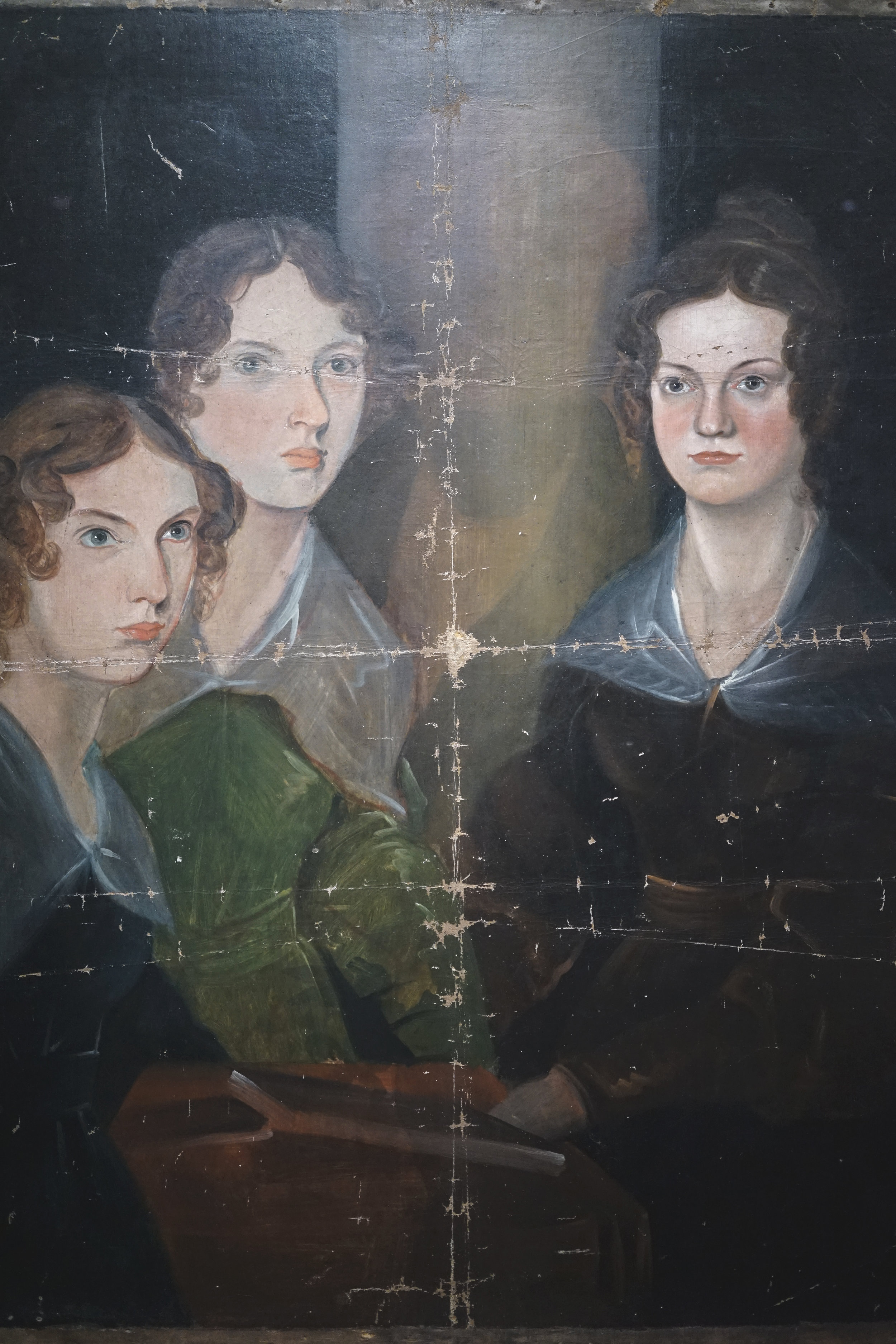 Branwell Brontë was about seventeen when he began this unfinished portrait, depicting his teenage sisters over a decade before they published the novels that made them famous. During the 1950's, infrared photography confirmed the presence of fourth figure- presumably a self-portrait that Branwell had chosen to efface- beneath the central pillar. As the oil paint has faded over time, the ghostly image has become ever more apparent to the naked eye.   The painting's condition reflects its history. Arthur Bell Nicholls, Charlotte's widower, took the work from Haworth parsonage to his new home in Banagher, Ireland, after Patrick Brontë's death. In 1914, Nicholls's second wife, Mary Ann, discovered the painting on top of a wardrobe in their farmhouse, where it had apparently lain folded for over fifty year. It was acquired by the National Portrait Gallery that year and placed on display to the public's great fascination. A century later, it is on view for the first time in North America.