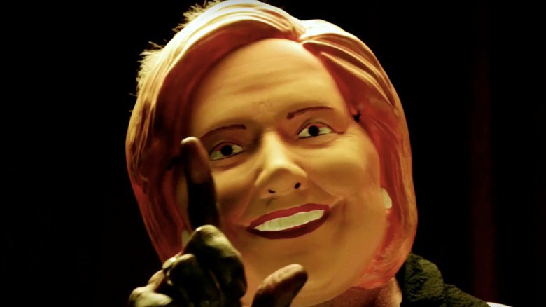 A person wearing a Hillary mask from the opening credits (Source: Google)