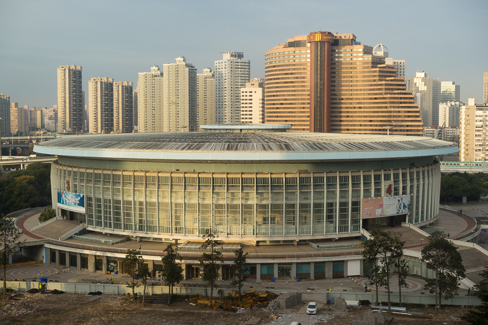 Construction works surround Shanghai's ageing Indoor Stadium, photographed here in the early morning light.