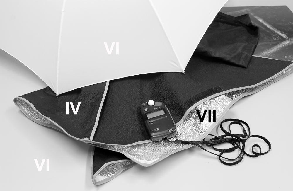 A one stop increase in exposure results in a 'whiter' umbrella, sitting on zone VI. Because we've now placed this on zone VI, the other areas we mentioned move up the scale accordingly: we've got a zone IV black area, a zone VII foil inner and a zone VI table top. We could place the umbrella on VII to visually bring it more in line with what a white umbrella should look like, but the consequence would be a mid-grey black area on the softbox cover, which is actually black. A zone system approach to the problem would be to go with the second of the two exposures, but increase development to make the umbrella lighter.