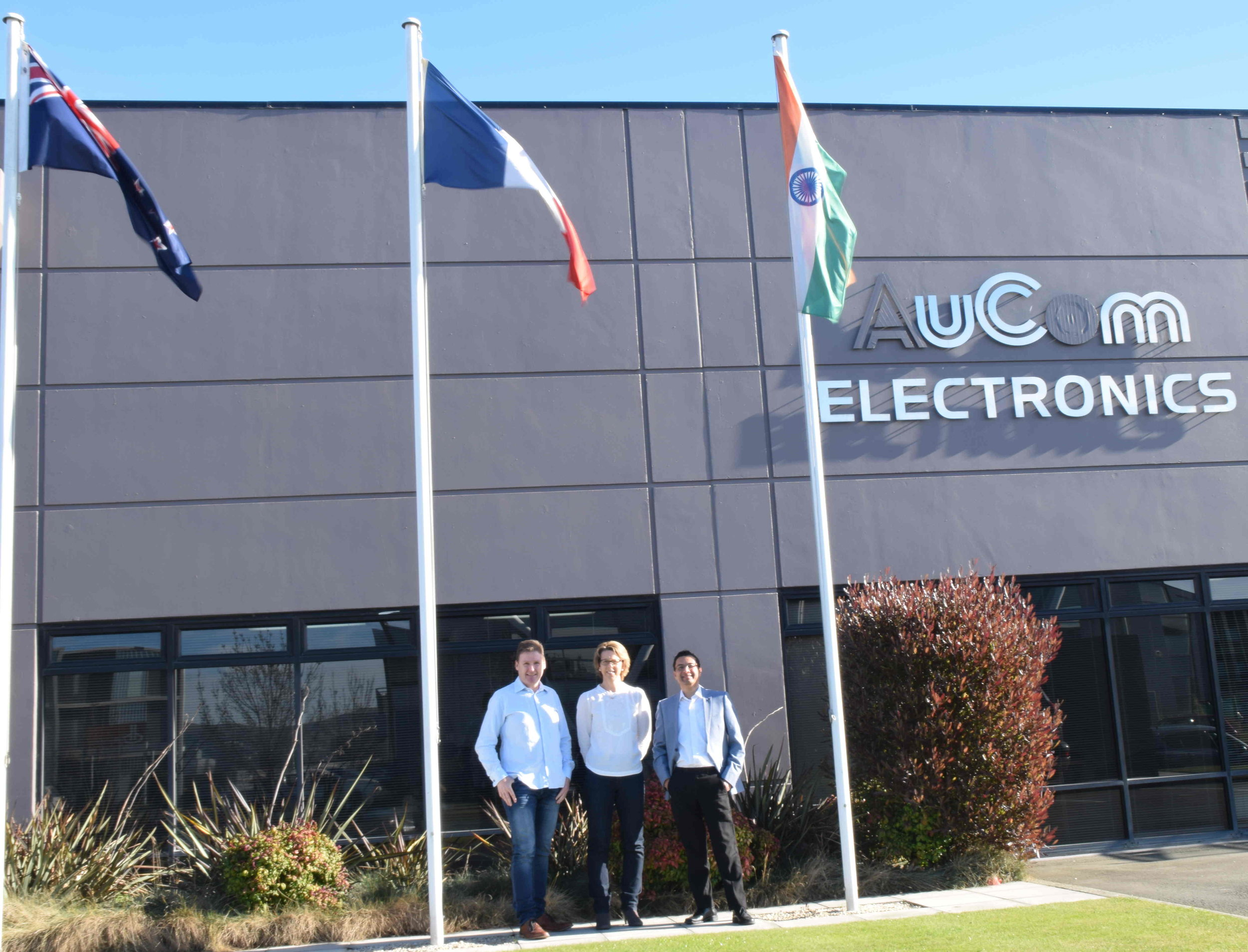 Indian flag outside AuCom's office; Brent Archer (left), with Shirish (right), and Mandy (company's HR Head)