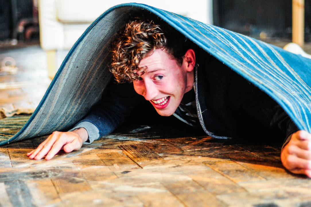 Young boy peeping out from under a rug