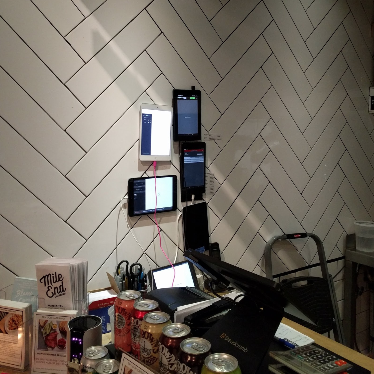 Multiple iPads for Seamless, Grubhub, Amazon, Foodkick, Uber Food hang on the wall of a restaurant, where a service worker takes orders.