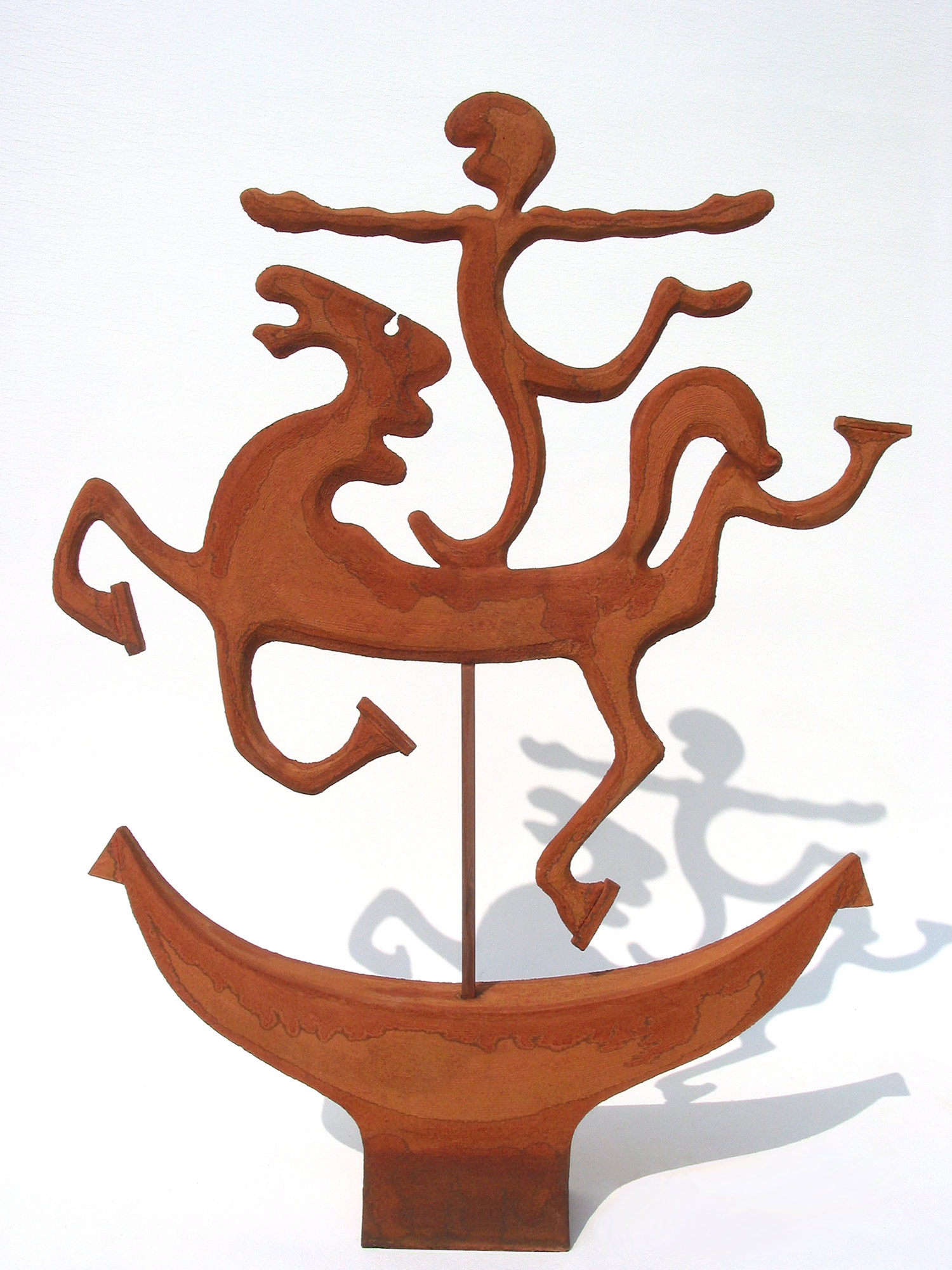 King Creole   ©  87 cm high x 66 cm wide  Unique  Flying over a Norse-like vessel, a Celtic war-horse – simple, like an iron-age chalk downs carving, gallops with a standing rider on board.  The rider is based on the cave scratching of an even earlier art form to become a Neolithic King with an Elvis quiff or a primitive mouth.  The weathervane arms point east and west and echo the Christian cross.