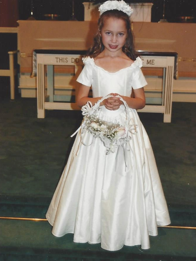 Brielle was a flower girl in 1995. Her silk duppioni dress was designed to match her cousin's wedding gown silhouette. Hand gathered silk petal flowers adorned the dress.