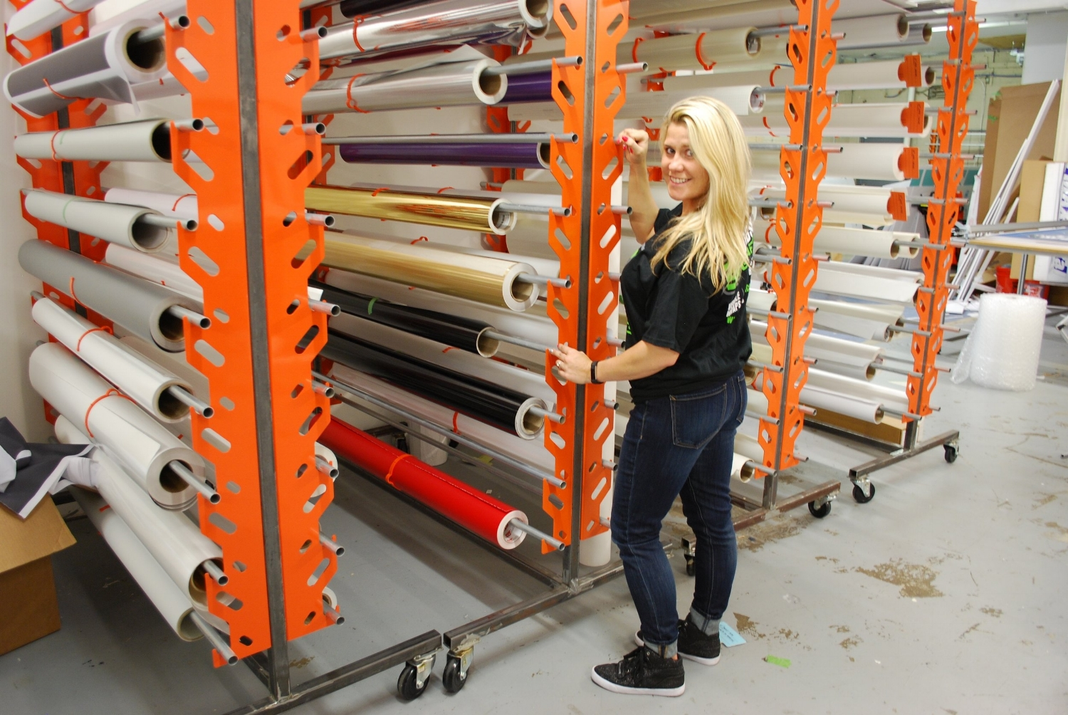 There is definitely something hot about this pic! Love the orange racks of different color vinyls;)I wish I had racks like these for my many silk fabrics at Headpiece.com, but our facility is not the size of Bombshell Graphics. I was amazed at the size of their space. My dad, who was a printer, would have loved a tour of their shop and to see how much technology has progressed since the days of adding ink to the printing press rollers.