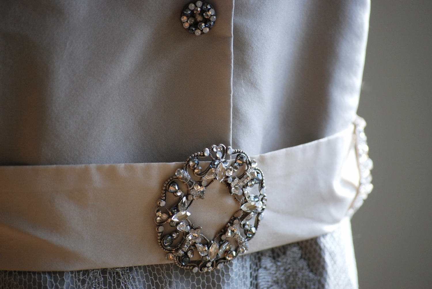 I wanted a Jackie Kennedy style with a menswear influence. I handmade the buttons and belt buckle The soft toned palette of gray, ivory, and taupe was in my mind from the beginning. My skirt was made of iridescent silk taffeta with a metallic silver and ivory French lace overlay. I loved everything about it!
