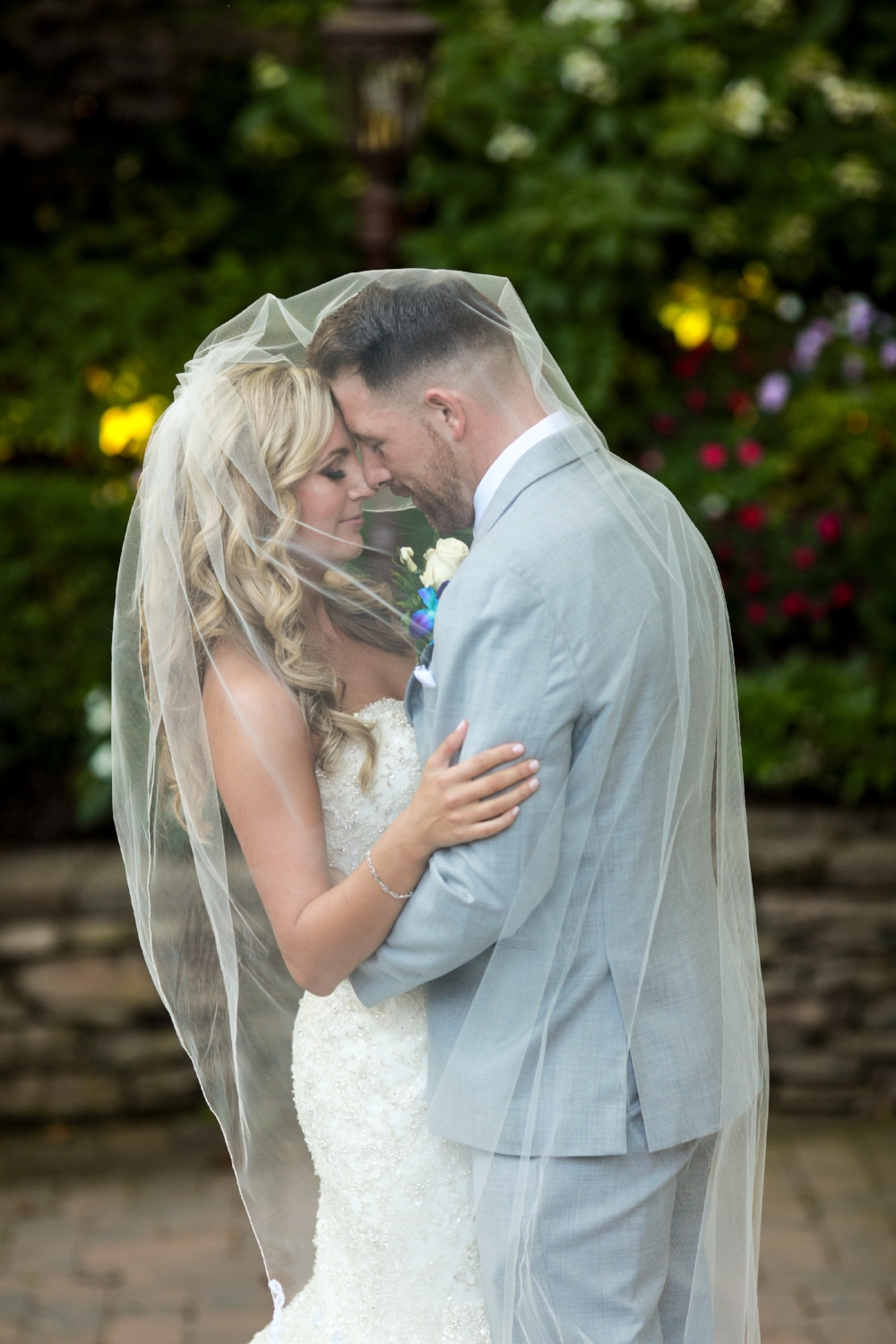 Often we see photos of the bride and groom under the veil. This one is different. This day they were wrapped in the veil of a mother's love.