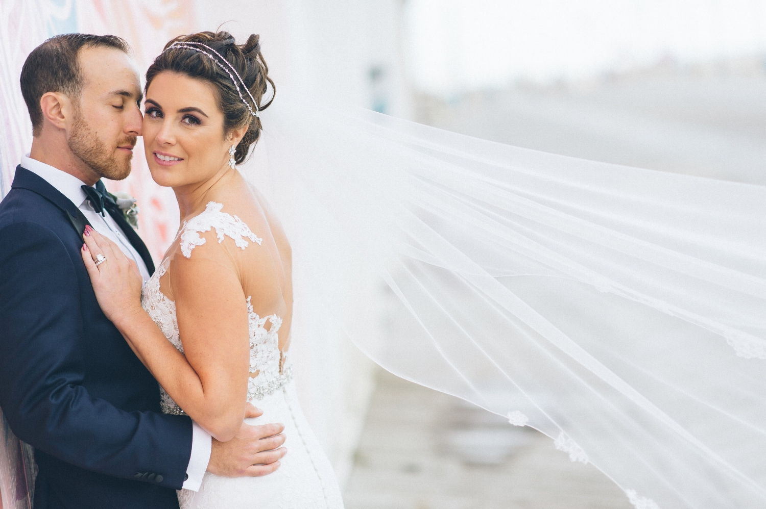 """We designed Lauryn's """"Janel"""" headpiece and added white opal and a touch of pearl. Her veil was delicately edged with pieces of hand-cut Alençon and narrow Leavers lace. The final touch was the tedious application of Swarovski stones and white opals."""