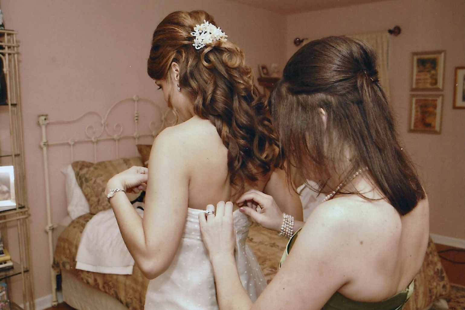Maid of honor, Amy, helps her sister Dana get wedding ready. This photo was taken nine years ago, but Dana's hair and accessory style are still current.